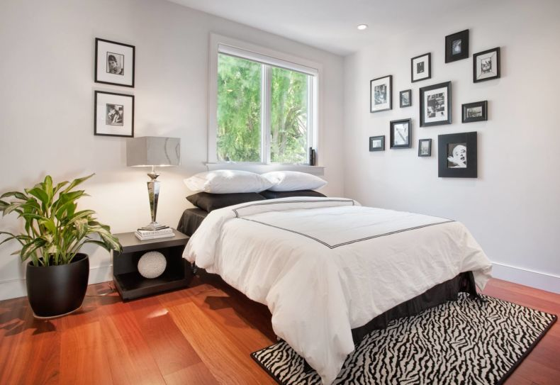 simple-window-between-picture-and-double-bed-on-wooden-floor-in-black-and-white-bedroom