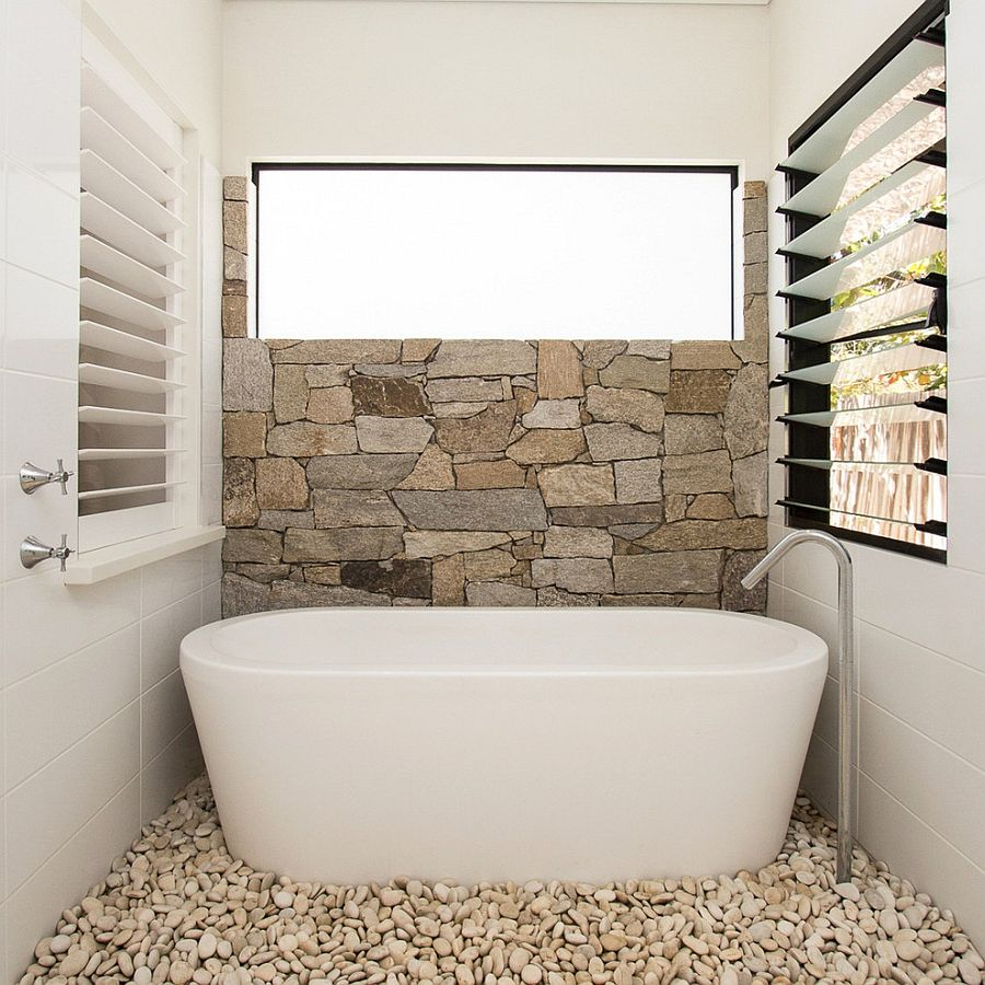 half-wall-in-natural-stone-and-pebbles-on-the-floor-turn-the-the-small-bathroom-into-a-relaxing-hub