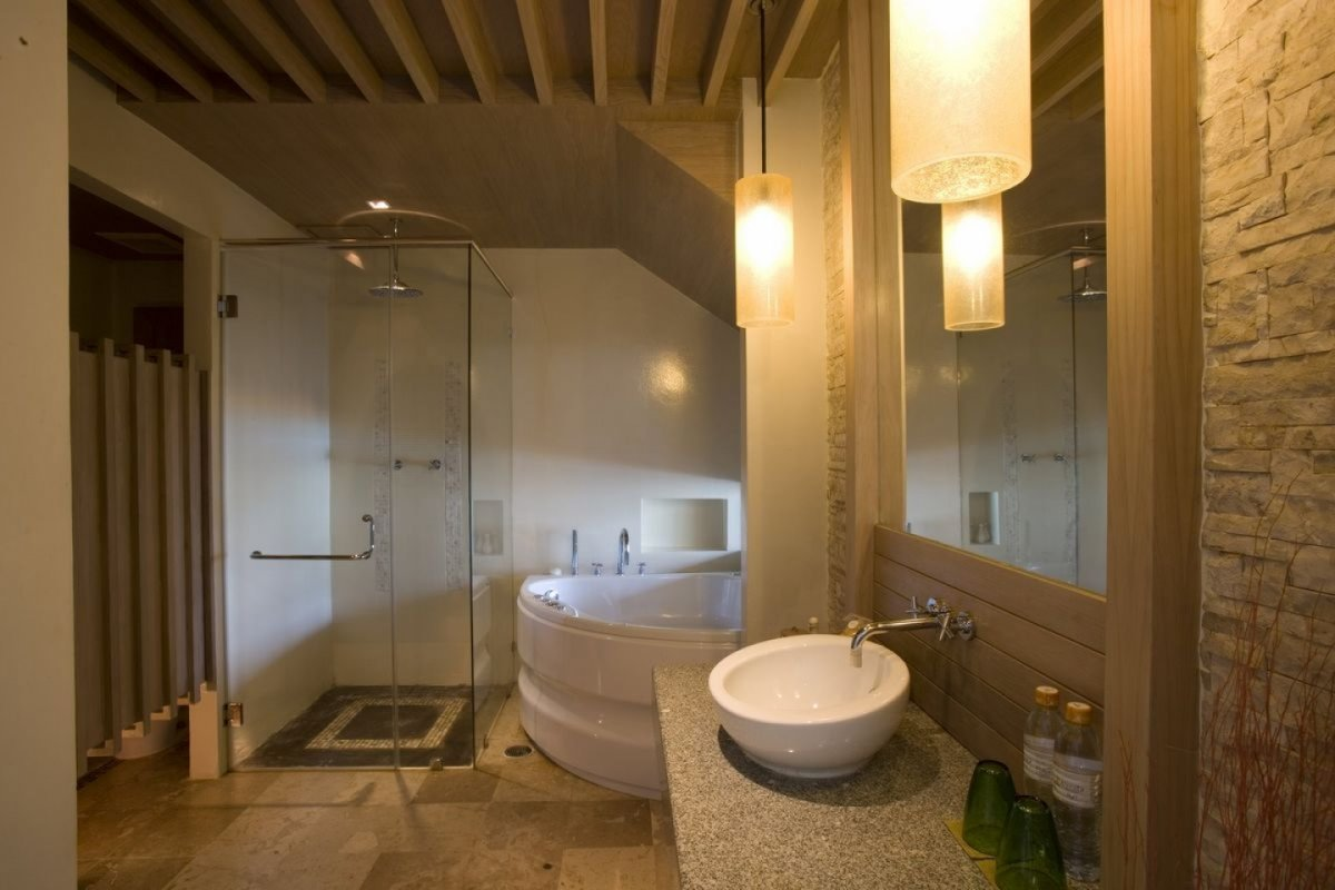 small-spa-bathroom-with-corner-bathtub-and-frameless-glass-shower-screen-and-white-washbasin-and-large-mirror