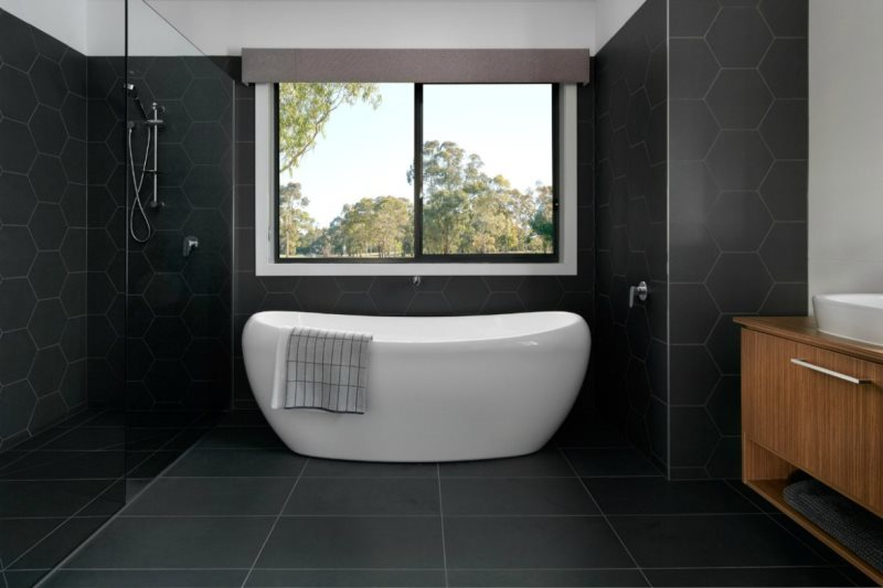 black-bathroom-hexagonal-black-wall-tiles-freestanding-bath-with-view-from-metricon