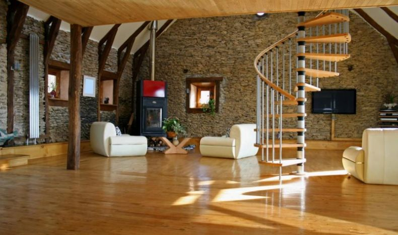 elegance-staircase-in-living-room-design-with-natural-stone-wall-decoration-including-pellet-sove-corner-including-beige-chair-on-wooden-floor-also-wooden-ceiling