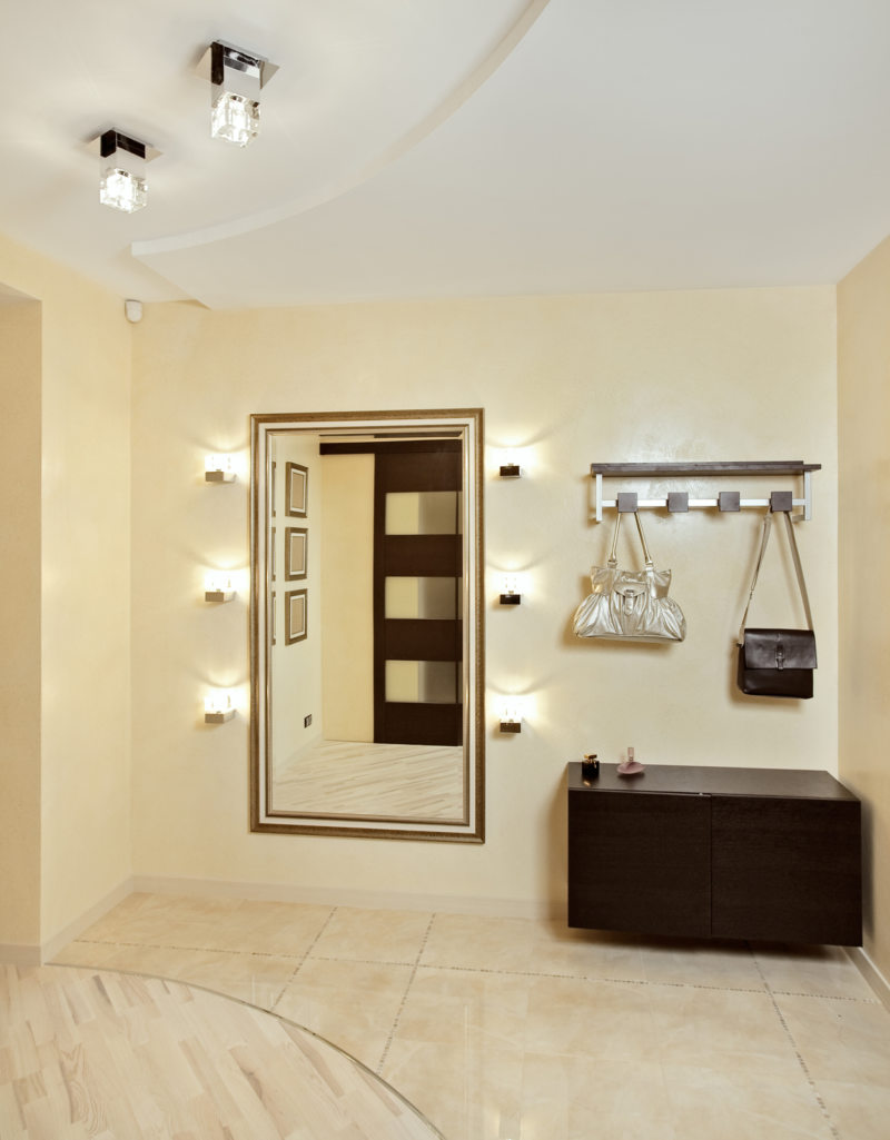 Hall in beige tones with hallstand and golden mirror